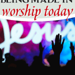 Church raising hands in worship with Jesus sign lit up
